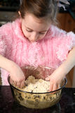 Mixing by hand. Young girl mixing food ingredients in a bowl with her hands Royalty Free Stock Photo