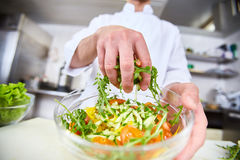 Mixing by hand. Chef mixing salad ingredients in bowl Stock Image