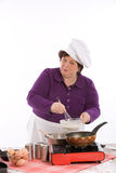 Mixing the ingredients. Female chef working above the stove mixing her ingredients Stock Photo