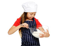 Mixing little chef. Adorable young chef girl mixing flour with whisk for baking and cooking isolated Stock Images