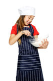 Mixing little chef. Adorable young chef girl mixing flour with whisk for baking and cooking isolated Stock Photo