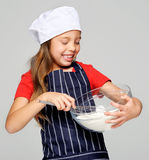 Mixing little chef. Adorable young chef girl mixing flour with whisk for baking and cooking isolated Stock Photos