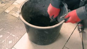 Mixing mortar in a bucket. Close - up of mixing concrete in a round bucket on a construction site stock video footage