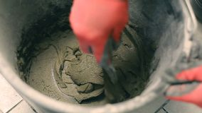 Mixing mortar in a bucket. Close - up of mixing concrete in a round bucket on a construction site stock footage