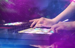Mixing music on midi controller with party club colors around. Hand mixing music on midi controller with party club colors around royalty free stock photography