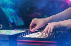 Mixing music on midi controller with party club colors around. Hand mixing music on midi controller with party club colors around royalty free stock photos