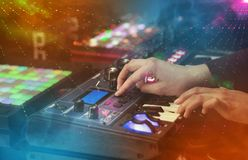 Mixing music on midi controller with party club colors around. Hand mixing music on midi controller with party club colors around royalty free stock images