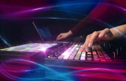 Mixing music on midi controller with wave vibe concept. Hand mixing music on midi controller with wave vibe concept stock photo