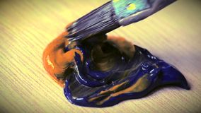Mixing the oil paint yellow and blue in the palette. Close-up stock footage