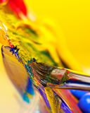 Mixing paint. Brush mixing paint on palette royalty free stock photography