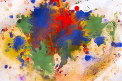Mixing of paints different colors on a white paper Royalty Free Stock Photography