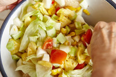 Mixing salad. Mixing all the salad ingredients Royalty Free Stock Photo