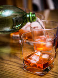 Mixing soft drink with alcohol, pouring into a glass tumbler wit Royalty Free Stock Images