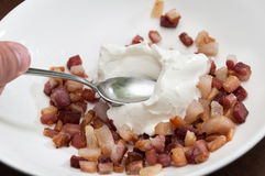 Mixing sour cream with fried bacon slices Stock Image
