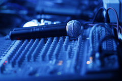 Mixing studio with microphones. Two microphones on a studio mixing board toned in blue royalty free stock photography
