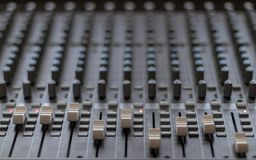 Front view of mixing console with sliders and red lights stock photo