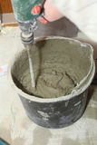 Mixing Tile adhesive or cement with a power drill Stock Images