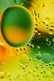 Mixing water and oil, beautiful color abstract background based on green and yellow circles, ovals, macro abstraction. Mixing water and oil, beautiful color Royalty Free Stock Photos