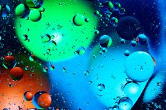 Mixing water and oil on a beautiful color abstract background gradient balls circles and ovals royalty free stock photography