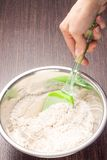 Mixing wheat flour in metallic bowl Royalty Free Stock Photo
