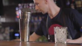 Mixologist de barman à l'aide du dispositif trembleur et faisant un cocktail d'alcool avec différentes boissons dans la belle bar banque de vidéos