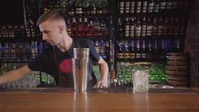 Mixologist del barista che per mezzo dell'agitatore e facendo un cocktail dell'alcool con differenti bevande nella bella barra mo stock footage