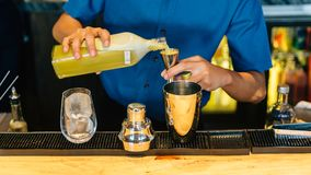 Mixologist making Yuzu cocktail with Shaker, Double Size Jiggers and drinking glass with ice cube on cocktail counter bar royalty free stock photo