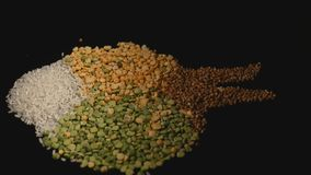 A mixture of cereals, peas, lentils, rice, buckwheat on black background stock video