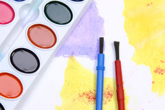 Mixture of colors. Watercolors and brushes on a painted background Royalty Free Stock Photo