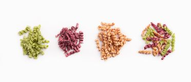 Mixture of different colorful fusilli isolated. Four heaps of different colorful fusilli pasta isolated on white background. Unusual creative meal, Italian Stock Image
