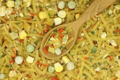 A mixture of dry noodles and vegetables with a wooden spoon. Abstract background Stock Photos