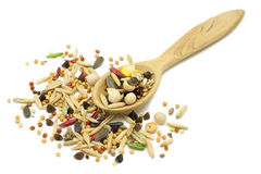 A mixture of grains and cereals in a wooden spoon. On a white background Royalty Free Stock Photo