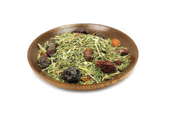 A mixture of herbs and berries in a wooden plate Stock Images
