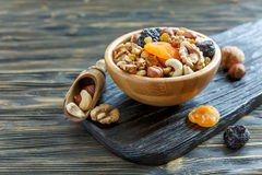 Mixture of nuts and dried fruit in a wooden bowl. Stock Photos
