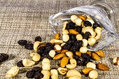 A mixture of nuts and dried grapes scattered on a glass table royalty free stock images