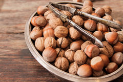 Mixture of nuts on metal plates with vintage orehokolom. Mixture of nuts on a metal plate with orehokolom on a wooden background royalty free stock photo