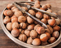 Mixture of nuts on metal plates with vintage orehokolom. Mixture of nuts on a metal plate with orehokolom on a wooden background royalty free stock photography