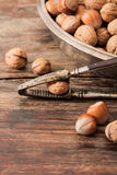 Mixture of nuts on metal plates with vintage orehokolom. Mixture of nuts on a metal plate with orehokolom on a wooden background royalty free stock images