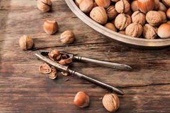 Mixture of nuts on metal plates with vintage orehokolom. Mixture of nuts on a metal plate with orehokolom on a wooden background stock photos