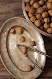 Mixture of nuts on metal plates with vintage orehokolom. Mixture of nuts on a metal plate with orehokolom on a wooden background stock image
