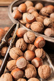 Mixture of nuts on metal plates with vintage orehokolom. Mixture of nuts on a metal plate with orehokolom on a wooden background stock photography