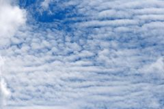 MIXTURE OF PATCHY AND RIBBED CLOUDS. Broken white clouds against blue sky Stock Images
