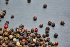 Mixture of pepper peas powder scattered on a slate plate. Closeup Royalty Free Stock Images