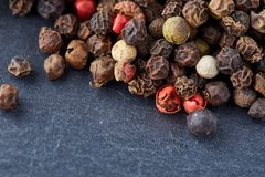 Mixture of pepper peas powder scattered on a slate plate. Closeup Royalty Free Stock Image