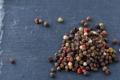 Mixture of pepper peas powder scattered on a slate plate. Closeup Royalty Free Stock Photo