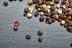 Mixture of pepper peas powder scattered on a slate plate. Closeup Stock Photos