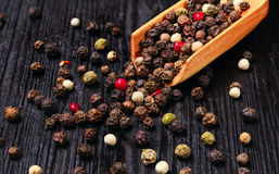 Mixture of peppercorns scattered on the wooden background Stock Images