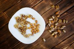 A mixture of pistachios, walnuts and almonds lies in a white plate on a wooden table made of pine boards. Farm harvest stock photos