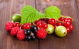 A mixture of ripe berries on a wooden table. Summer Still Life. Raspberries, gooseberries, currants close-up. Stock Photos