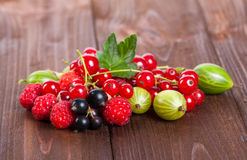 A mixture of ripe berries on a wooden table. Summer Still Life. Raspberries, gooseberries, currants close-up. Royalty Free Stock Image